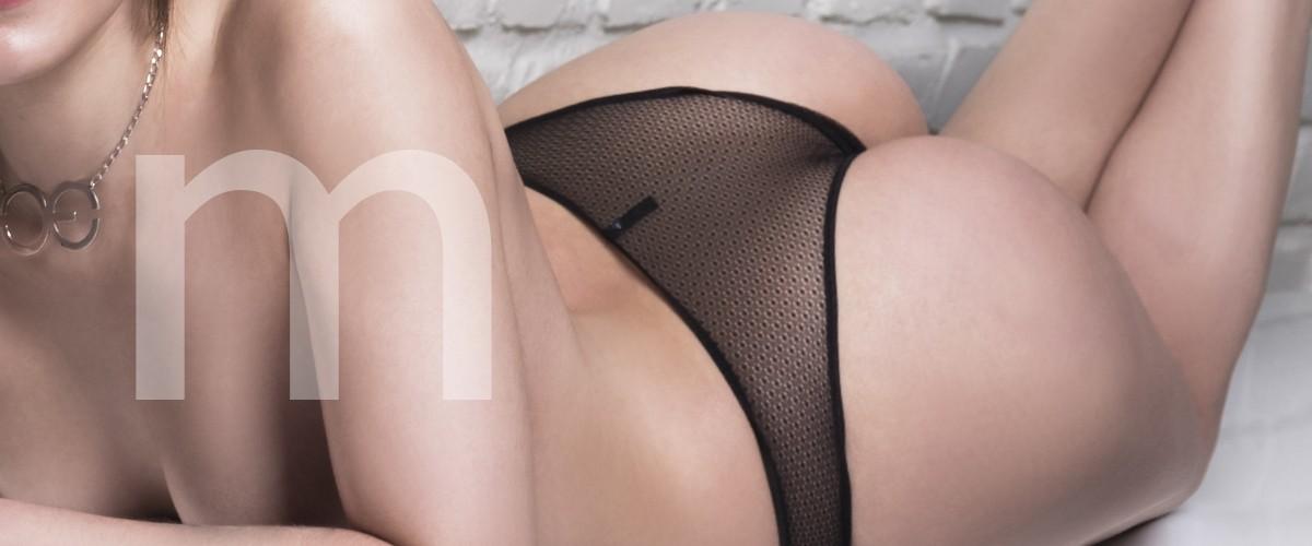 Margaret chica de compaía catalana en ropa interior con un conjunto negro, tumbada en un sofá